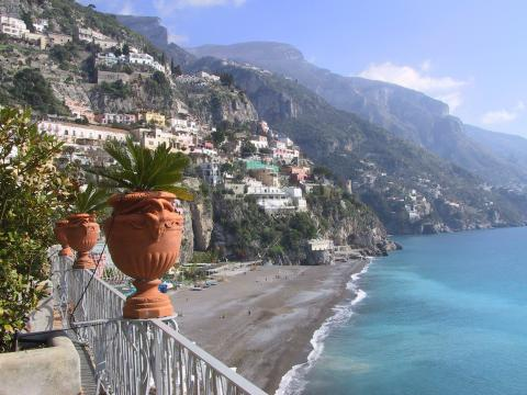 Clay pottery on a balcony overlooking the cliffs and azure waters of the Amalfi coast
