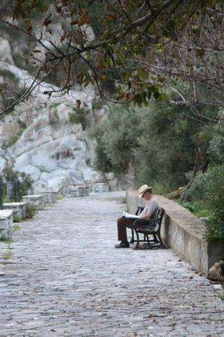 Man on a solitary bench on a stone road