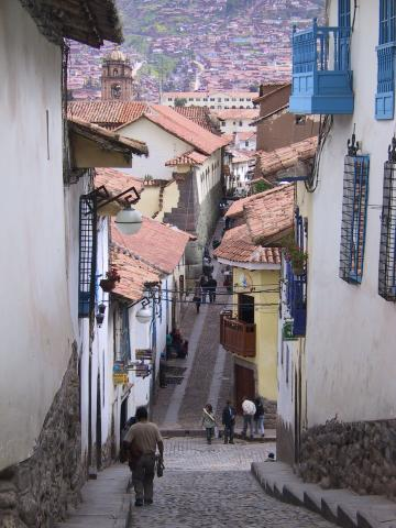 A man walks down a steep street with red roofs on the horizon