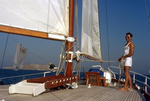 Man works the sails on the deck of a yacht