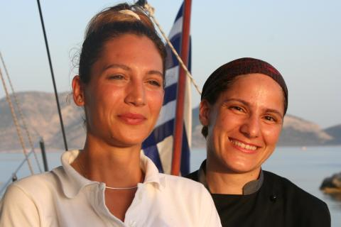 Two women smile in the sun aboard a yacht