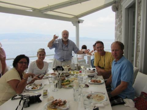 Leftheris Papageorgiou raises a toast at a group dinner by the sea