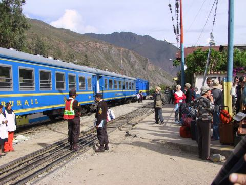 A blue train stops below the mountains.
