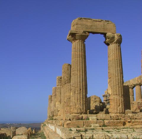 Golden columns from the ancient world stand out against the deep blue sky.