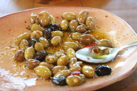 A spoon sits amidst fresh olives and olive oil in a hand-crafted bowl.