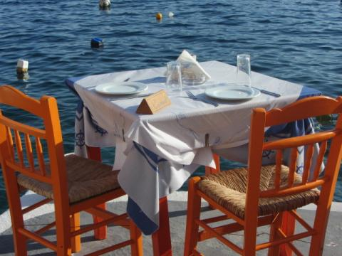 Reserved white linen restaurant table by the sea.